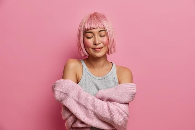 Vrouwen, tederheid, troost. aangename rozeharige aziatische vrouw omhelst zichzelf, sluit de ogen, voelt gezelligheid in een zachte trui, staat