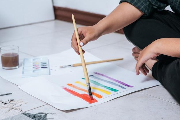 Vrouwen tekenen en schilderen water op papier.
