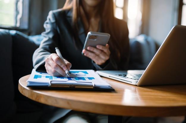 Vrouwen tellen munten op rekenmachine uit het spaarvarken. hand met pen bezig met rekenmachine om op bureau te berekenen over de kosten op kantoor aan huis.