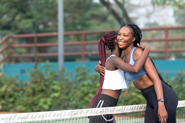 Vrouwen tennissers knuffelen