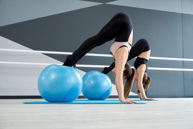Vrouwen trainen buikspieren met behulp van fitnessballen