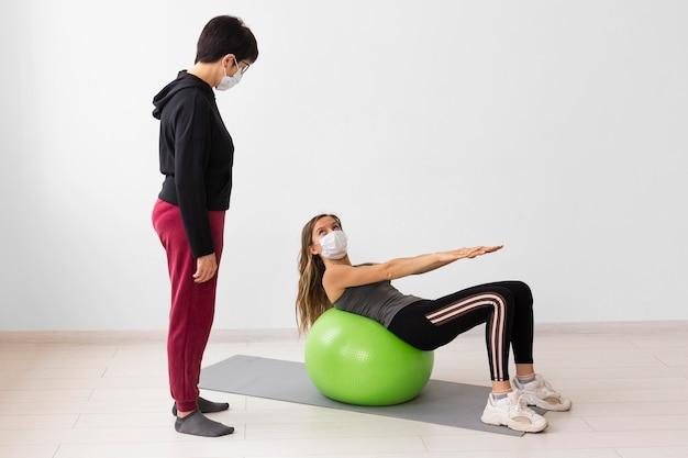 Vrouwen trainen op een fitnessbal terwijl ze medische maskers dragen