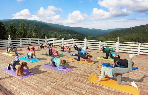 Vrouwen trainen op fitnessles, oefenen op matten.