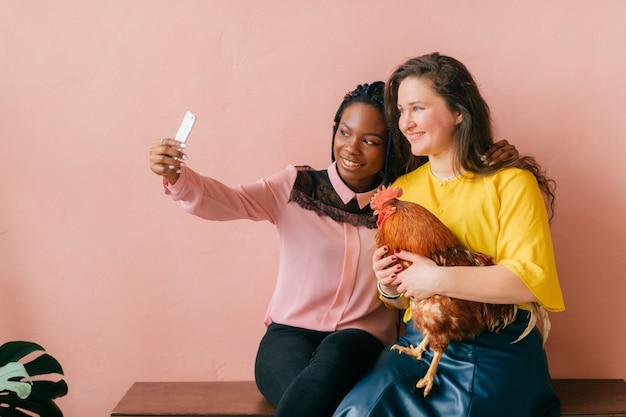 Vrouwen tussen verschillende rassen met kip in handen maken selfie over roze muur