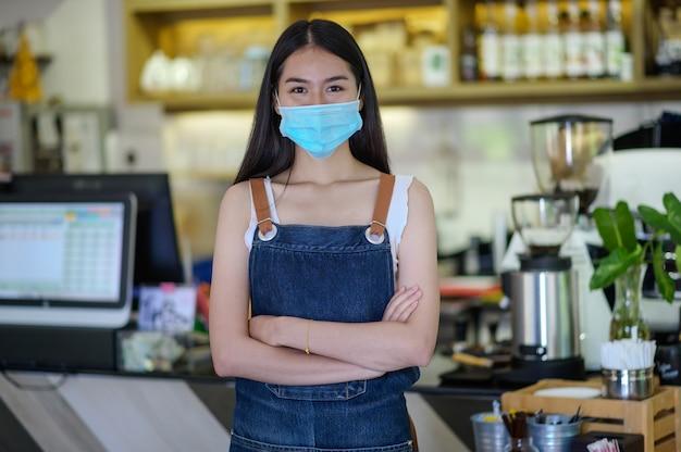 Vrouwen van de nieuwe generatie die een gezichtsmasker dragen, doen kleine zaken in de toonbank van de coffeeshop