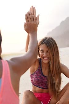 Vrouwen van gemengd ras geven elkaar een high five, omdat ze in een goede bui zijn