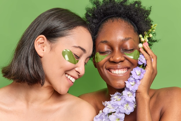 Vrouwen van gemengd ras glimlachen breeduit hydrogelpleisters aanbrengen onder de ogen zorg voor uiterlijk houd bloem vast