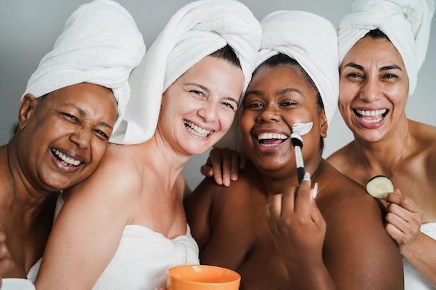 Vrouwen van meerdere generaties die plezier hebben met het aanbrengen van gezichtsmaskers op hun gezicht - hoofdfocus op het gezicht van de blanke vrouw