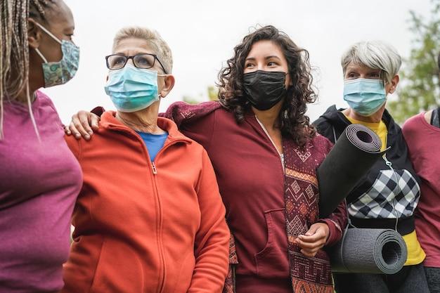 Vrouwen van meerdere generaties die samen plezier hebben na sporttraining buiten tijdens de uitbraak van het coronavirus - hoofdfocus op het gezicht van het middelste meisje