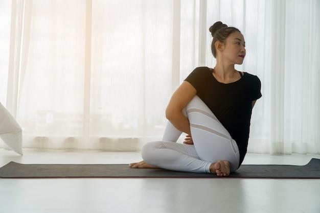 Vrouwen van middelbare leeftijd doen yoga in de slaapkamer in de ochtend,