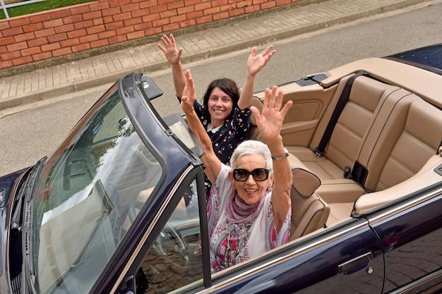 Vrouwen van verschillende generaties gelukkig in een converteerbare auto