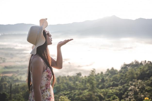Vrouwen verhogen handen in de vrije ruimte op de bergen