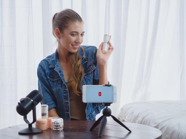 Vrouwen verkopende schoonheidsmiddelen online met computer, die zaken in haar huis doen