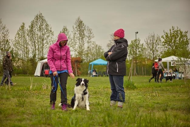 Vrouwen vermaken zich in het park met de hond