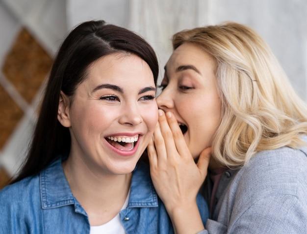 Vrouwen vertellen een geheim en lachen