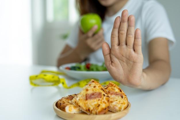 Vrouwen verwerpen en duwen pizza en eten appel, groentesalades die voor hen worden geplaatst. vrouwen kiezen voedingsmiddelen die gezond zijn voor het lichaam.