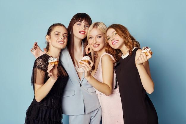 Vrouwen vieren het feest met plezier lachen en taarten eten onder de vliegende confetti. meisjes poseren en glimlachen op een blauwe achtergrond, vrolijke emoties, glimlachen en lachen