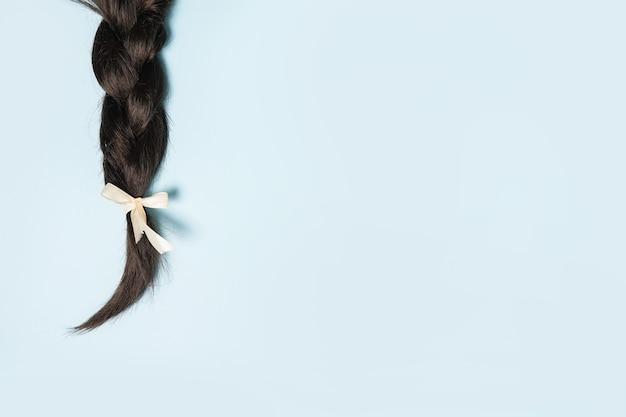 Vrouwen vlecht met strik op een blauwe achtergrond. kopieer ruimte
