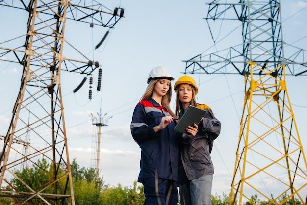 Vrouwen voeren een inspectie uit van apparatuur en hoogspanningsleidingen