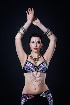 Vrouwen voert buikdans in etnische kleding op zwarte achtergrond, studio-opname
