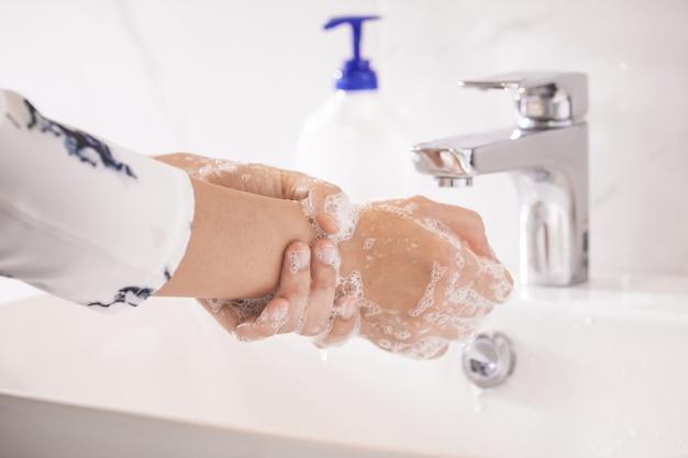 Vrouwen wassen handen met antibacteriële zeepreiniger of alcoholgel ter voorkoming van corona covid-19-virussen. hygiëne om de verspreiding van ziektekiemen en bacteriën te stoppen en infecties corona covid-19 virus te voorkomen.