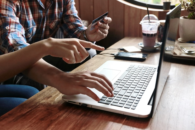 Vrouwen wijzen op man die online winkelt met creditcard en laptop
