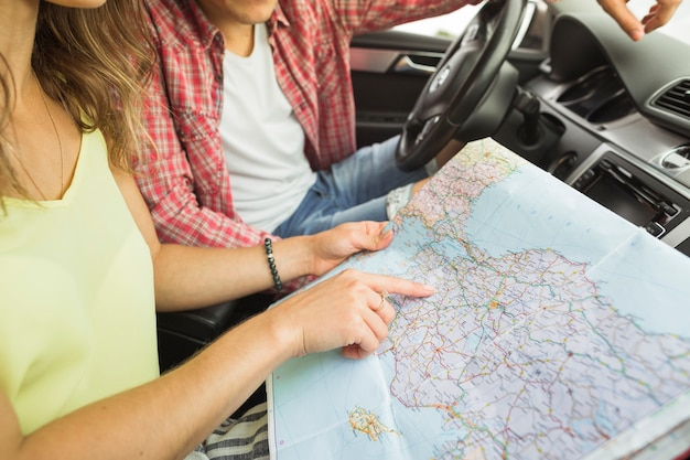 Vrouwen wijzende vinger op de kaart van de plaatsnavigatie met de mens in de auto