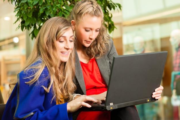 Vrouwen winkelen in winkelcentrum met laptop