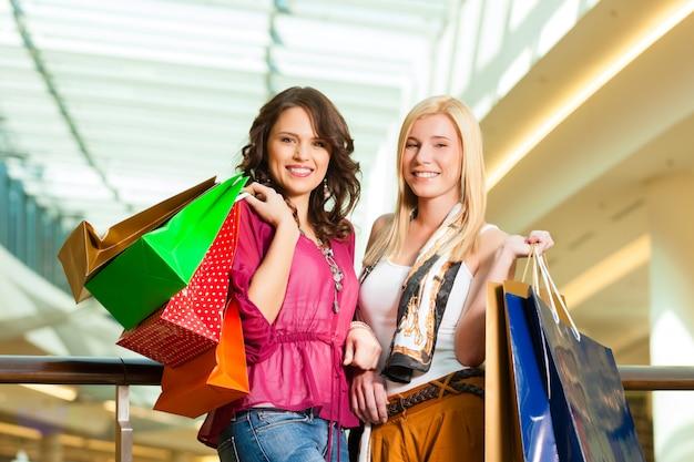Vrouwen winkelen met tassen in winkelcentrum