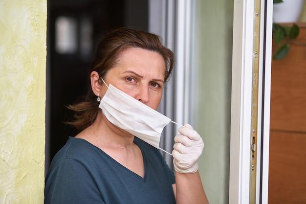Vrouwen zetten een ademhalingsmasker op. arts vrouw zet op gezichtsmasker en kijkt naar de camera.