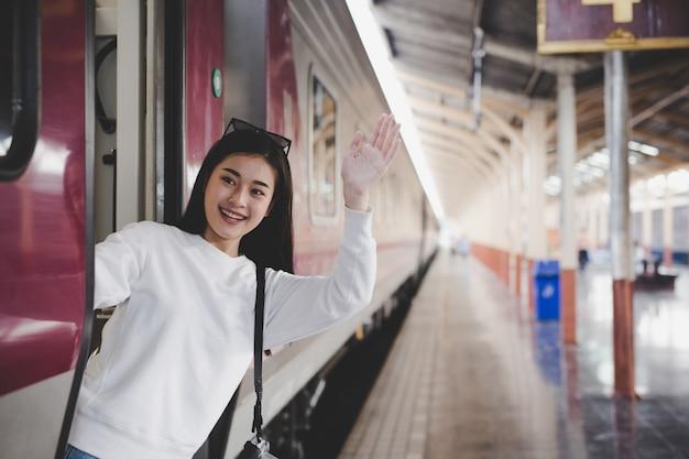 Vrouwen zijn blij tijdens het reizen op het treinstation. toerisme concept