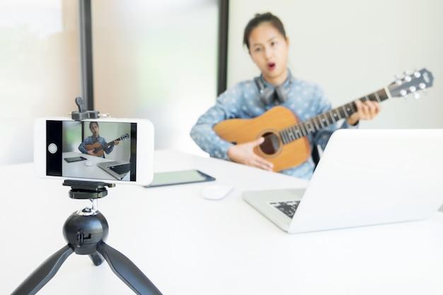 Vrouwen zingen een liedje met gitaar in handen, gebruik camera om live video naar sociaal netwerk uit te zenden via internet thuis.
