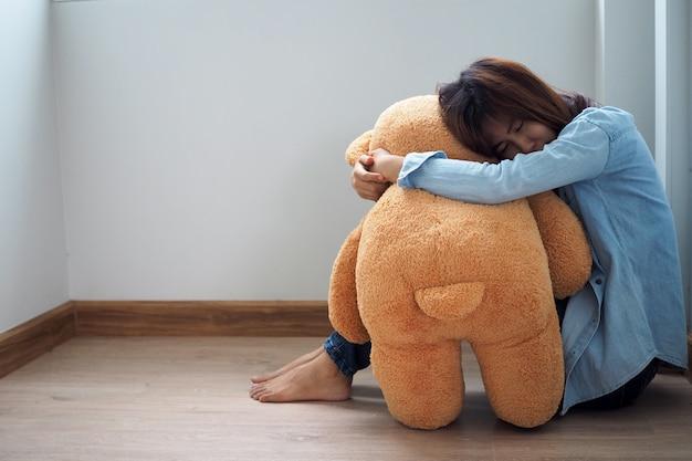 Vrouwen zitten droevige knuffelende teddyberen