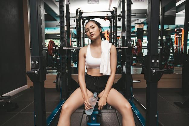 Vrouwen zitten en ontspannen na het sporten. houd een waterfles vast en draag een witte doek in de nek.