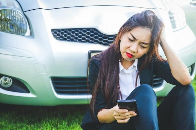 Vrouwen zitten gestrest terwijl ze de verkeerde route rijden mobiele telefoons bekijken zonder signalen kan de juiste weg niet vinden