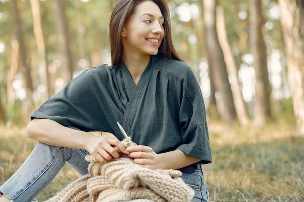 Vrouwen zitten in een zomer park en breien