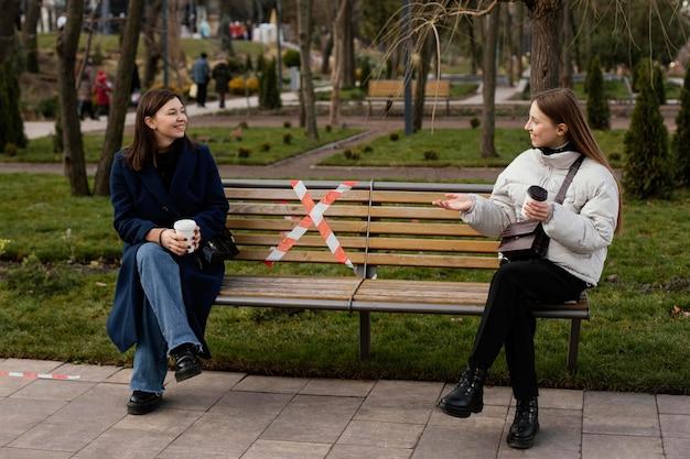 Vrouwen zitten op afstand en dragen een masker