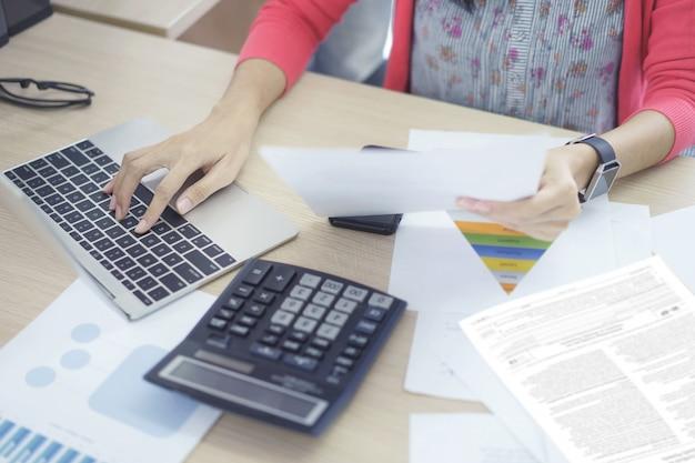 Vrouwenaccountant die aan rekeningen werken die belastingsinkomenskosten in bedrijfsanalyse plannen