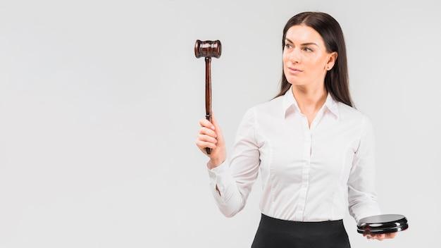Vrouwenadvocaat die zich met in hand hamer bevinden