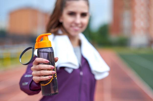 Vrouwenagent met handdoek die en drinkwater van een fles rusten na het uitwerken van spoorlooppas van stadion