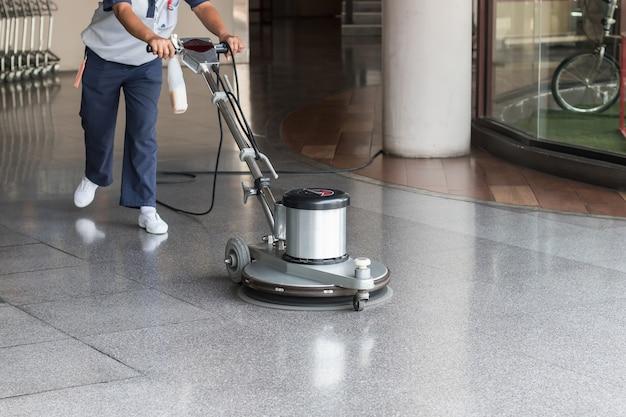 Vrouwenarbeider die de vloer met oppoetsende machine schoonmaken