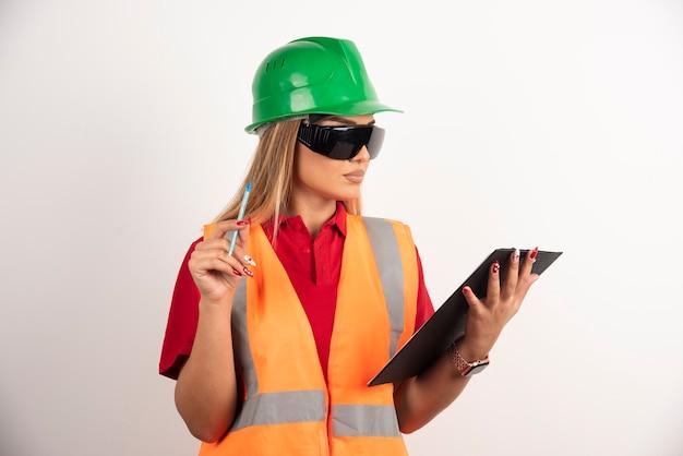 Vrouwenarbeider die een potlood met klembord houdt.