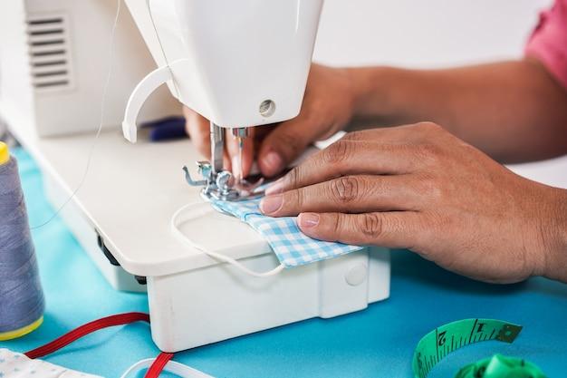 Vrouwenarbeider die naaimachine met behulp van terwijl het maken van gezichts medische maskers tijdens coronavirusuitbraak - naar huis gemaakt productieconcept