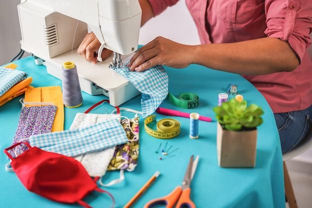 Vrouwenarbeider die trendy gezichtsmaskers naaien