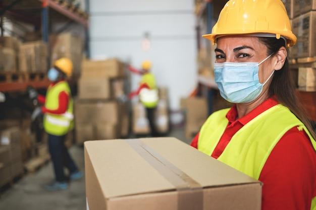 Vrouwenarbeider in magazijn die bezorgdozen laadt terwijl ze een veiligheidsmasker draagt voor coronaviruspreventie