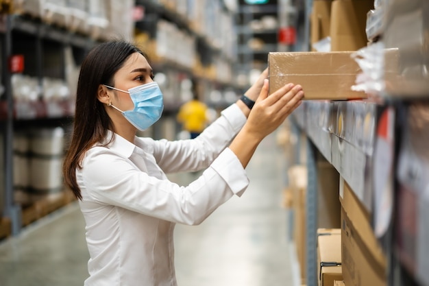 Vrouwenarbeider met medisch masker die inventaris in het magazijn controleert tijdens coronavirus-pandemie