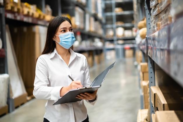 Vrouwenarbeider met medisch masker klembord vasthouden en inventaris controleren in het magazijn tijdens coronavirus pandemie