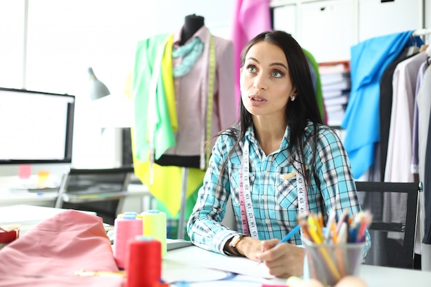 Vrouwenarbeider op servicepunt die bestellingen voor kledingreparaties ontvangt, communiceert met klant