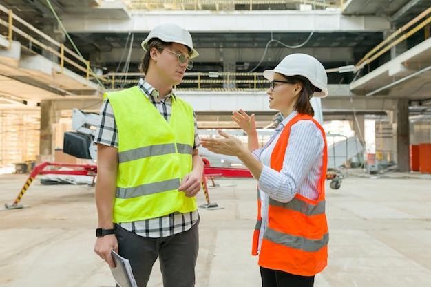 Vrouwenarchitect en man bouwer bij bouwwerf