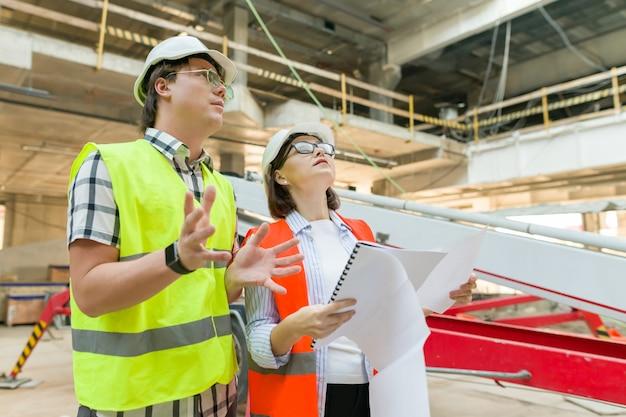 Vrouwenarchitect en man bouwer bij een bouwwerf